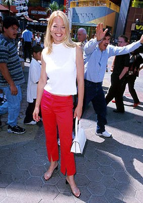 Premiere: Jeri Ryan pauses for a picture while the man behind her has apparently just been told that he looks like Dennis Farina one too many times at the Universal City premiere of Universal's The Ad