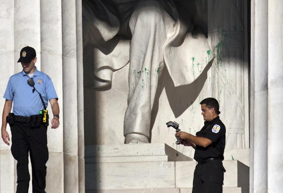 U.S. Park Police close off the Lincoln Memorial to visitors after someone splattered green paint on the statue and the floor area, in Washington, Friday, July 26, 2013. Police say the apparent vandalism was discovered early Friday morning. No words, letters or symbols were visible in the paint. (AP Photo/J. Scott Applewhite)