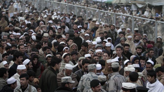 Afghan people stand in the main border crossing of Torkham, between Afghanistan and Pakistan east of Kabul, Afghanistan, Saturday, Dec. 29, 2012. Today is the second day that Torkham the main border between Afghanistan and Pakistan is closed by Pakistani authorities, hundreds of trucks, cars plus several hundred people including, women, children, elders and especially sick people who are going from Afghanistan to Pakistan for treatment are waiting for the border to open, there are reports of at least three civilians being killed in Afghanistan side and more than five others being killed in Pakistan side since the border is closed because of the cold weather and heavy rain (AP Photo/Rahmat Gul)