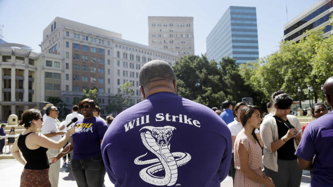 Union leader Dwight McElroy, center, conducts interview alongside fellow union members in Oakland, Calif., Friday, June 28, 2013. Two of San Francisco Bay Area Rapid Transit's largest unions gave notice that they plan to go on strike if they don't reach a new contract deal over the weekend. (AP Photo/Marcio Jose Sanchez)