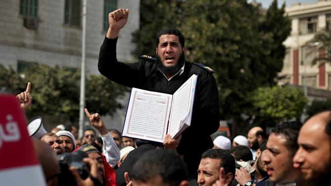 An Egyptian bearded police officer chants slogans and holds a copy of the Quran during a Salafi Muslim protest in support of the bearded police officers who were prevented from carrying out their work in the interior ministry, in front of Abdeen presidential palace in downtown Cairo, Egypt, Friday, March 1, 2013. (AP Photo/Khalil Hamra)