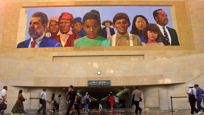 """FILE - In this Aug. 30 2000, file photo, commuters walk into a tunnel at Los Angeles's  Amtrack-Metrolink Union Station under the mural """"City of Dreams/River of History"""" by artist Richard Wyatt, showing the diversity of California's population.  Union Station is renowned for both its beauty and distinctive fusion of Spanish Colonial and Art Deco architecture when it opened in 1939. With its huge waiting room and landscaped gardens, the place, still a working train station, offers a perfect venue for reading, resting, people watching or taking a lunch break. (AP Photo/Damian Dovarganes, File)"""