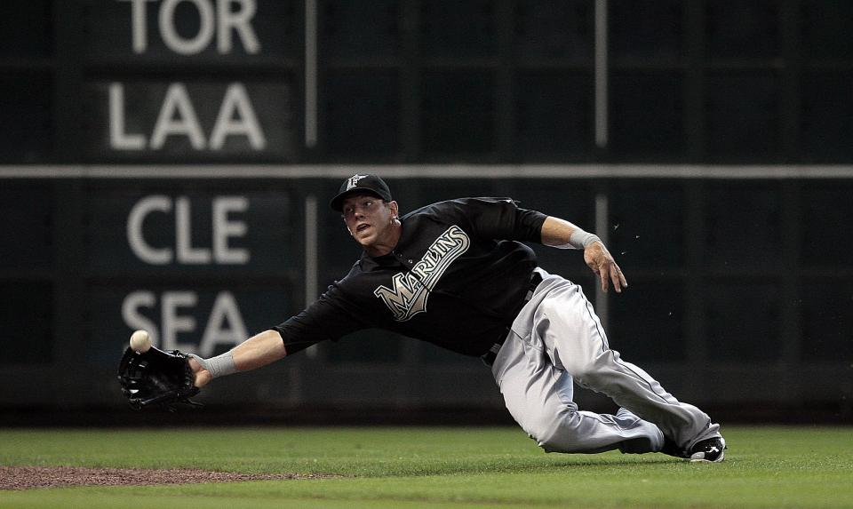 Florida Marlins left fielder Logan Morrison (20) makes a diving attempt on a fly ball hit down the line by Houston Astros' Michael Bourn but comes up short in the first inning of an MLB baseball game on Sunday, April 10, 2011, in Houston. (AP Photo/Bob Levey)
