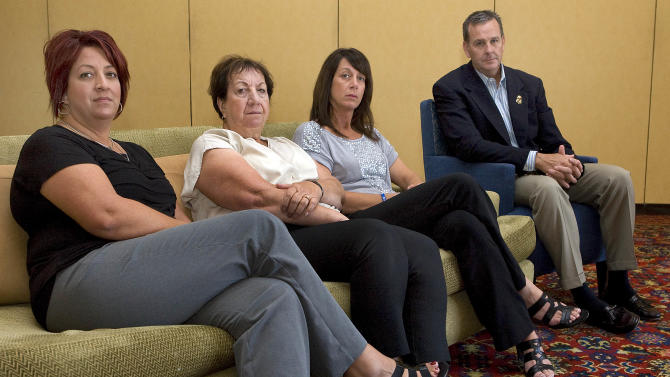 In this Sunday, Sept. 16, 2012 photo, members of Brian Terry's family, from left to right, Michelle Balogh, left, Josephine Terry, Kelly Willis and Robert Heyer, far right, pose at the Marriott-Starr Pass Resort in Tucson, Ariz. Family members of Terry, an Arizona U.S. Border Agent killed in connection with a botched gun-smuggling operation, say they won't have closure until someone is held accountable for his death. (AP Photo/John Miller)