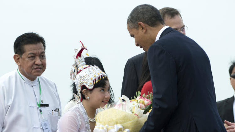 U.S. President Barack Obama is presented with flowers as he arrives at Yangon International Airport in Yangon, Myanmar, on Air Force One, Monday, Nov. 19, 2012. This is the first visit to Myanmar by a sitting U.S. president. (AP Photo/Carolyn Kaster)