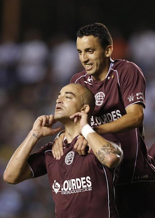 Santiago Silva, left, of Argentina's Lanus celebrates with teammate Jorge Ortiz after scoring against Paraguay's Libertad at a Copa Sudamericana soccer game in Asuncion, Paraguay, Thursday, Nov. 21, 2