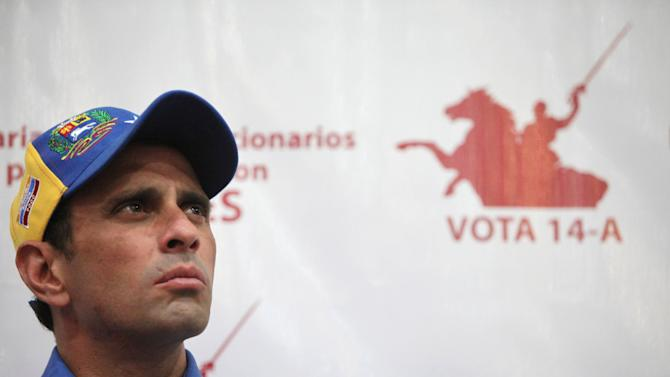 "Opposition presidential candidate Henrique Capriles looks on during a meeting with former supporters of late President Hugo Chavez in Caracas, Venezuela, Wednesday, April 3, 2013. Behind the wall shows an image referring to independence hero Simon Bolivar and reads in Spanish ""Vote April 14.""  Other parts of the sign, partially covered, read ""Bolivarians and revolutionaries for the homeland with Capriles.""  Venezuela will hold a presidential election to replace late President Hugo Chavez on April 14. (AP Photo/Fernando Llano)"