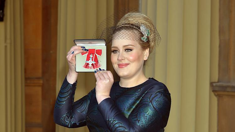 British singer Adele Adkins holds her MBE for services to music presented to her by the Prince of Wales at Buckingham Palace in London, Thursday, Dec. 19, 2013. (AP Photo/John Stillwell, Pool)