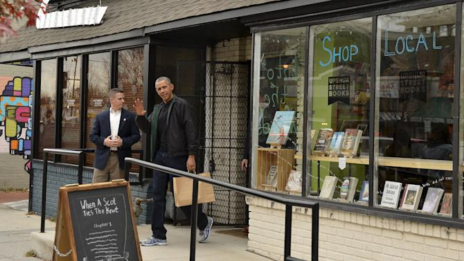 U.S. President Barack Obama waves as he departs Upshur Street Books after purchasing books with daughters Malia and Sasha, in Washington