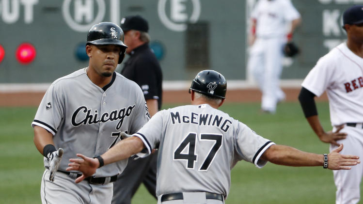 Chicago White Sox's Jose Abreu receives congratulations from Chicago White Sox third base coach Joe McEwing (47) after his solo homer in the first inning of a baseball game against the Boston Red Sox at Fenway Park in Boston, Wednesday, July 9, 2014. (AP Photo/Elise Amendola)