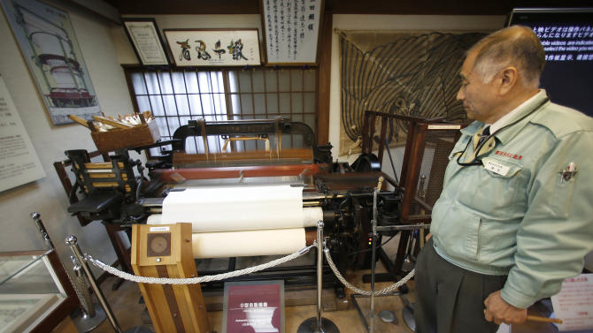 In this photo taken Monday, Feb. 18, 2013,  Sakichi Toyoda Memorial House manager Tadashi Kanzaki stands by a Type G automatic loom invented by Sakichi Toyoda, father of Toyota Motor Corp. founder Kiichiro Toyoda and great-grandfather of current President Akio Toyoda, at the renovated birthplace of Sakichi Toyoda in Kosai, central Japan. Sakichi Toyoda invented the automatic loom in a backyard shed, mainly because he wanted to help his mother, who often was weaving in their home. Those around him, including his carpenter father, thought he was crazy and laughed at him. When Kiichiro Toyoda wanted to develop cars in 1933, not just keep making the by-then successful looms, people again laughed. Back then, Japan only had imported cars like GMs and Fords. (AP Photo/Shizuo Kambayashi)