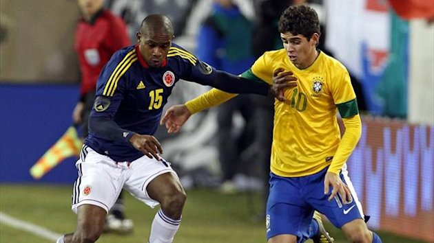 Brazil's Oscar fights for the ball with Colombia's Edwin Valencia during their international friendly in the US (Reuters)