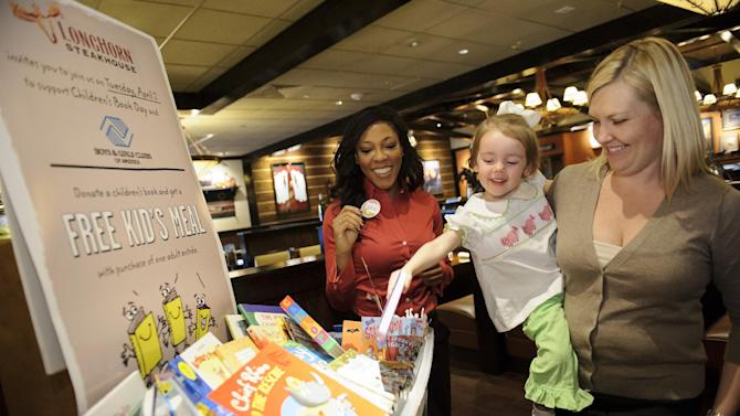 "IMAGE DISTRIBUTED FOR LONGHORN STEAKHOUSE - Atlanta-area LongHorn Steakhouse Managing Partner Lisa Hoggs smiles as Laine presents her book with her mother Tiffany in honor of International Children's Book Day on Tuesday, Apr. 2, 2013. Today only, LongHorn is offering a ""Give a Book, Get a Free Kid's Meal"" promotion, benefiting local Boys & Girls Clubs across the country. With each children's book donation, guests will receive a free kid's meal with the purchase of one adult entrée. (Paul Abell / AP Images for LongHorn Steakhouse)"