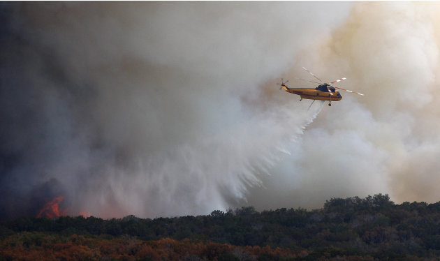 A helicopter drops water on a wildfire at Possum Kingdom Lake, Texas, Wednesday, Aug. 31, 2011. The wildfire that swept through the Possum Kingdom Lake neighborhood, one of several burning in Texas an