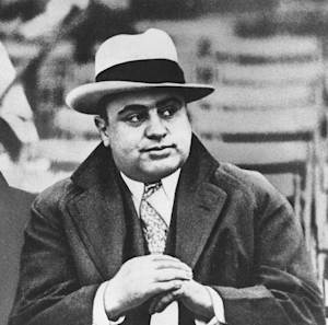 FILE - In this Jan. 19, 1931 black-and-white file photo Chicago mobster Al Capone watches a football game in Chicago. For a time, the Internal Revenue Service inspired awe and admiration in Americans, not just trepidation and lame jokes about death and taxes. Everyone loved it when revenue agents put away Capone, the Chicago underworld's master of brutality and bribe, in a coup so spectacular it scared other gangsters straight. But there's little love for the IRS anymore, and there hasn't been for ages. (AP Photo/File)