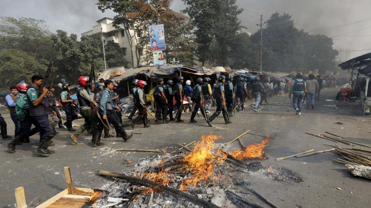 Police officers conduct a raid in an area after clashes with Jamaat-e-Islami party activists in Dhaka