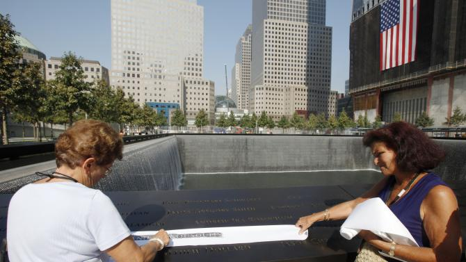 ADDS INFORMATION ABOUT THE PEOPLE IN THE PHOTO - Katina Velahos, right, watches as Zoe Kousoulis makes a rubbing of the name of her daughter Danielle Kousoulis, who was killed in the 9/11 terrorist attacks, from one of the panels inscribed with the victims' names on the first day that the 9/11 memorial plaza was opened to the public at the World Trade Center site in New York, Monday, Sept. 12, 2011. (AP Photo/Mike Segar, Pool)