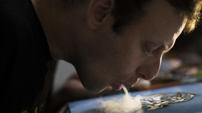 Brazilian artist Fernando de la Rocque blows marijuana smoke onto a stencil overlaying paper to create his art at his studio in Rio de Janeiro, Brazil, Monday Aug.  20, 2012. Some of Rocque's pot-stained prints are being sold for $2,500 each. A show featuring the work opened last week at a small alternative gallery in the stylish Ipanema neighborhood. It takes him a week to complete a single print  blowing about five joints' worth of smoke onto a paper daily.  (AP Photo/Felipe Dana)