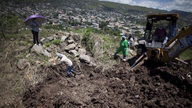 In this Aug. 18, 2012 photo, a judiciary morgue worker places a cross at the site of a mass grave after 25 unclaimed bodies were buried at the Divine Paradise cemetery in Tegucigalpa, Honduras.  Without coffins, morgues don't release bodies to the families and they end up in mass graves. This is why coffins are so valuable in Honduras, an impoverished country with a sky-high murder rate, so much that critics say they have become tools for political campaigning.  (AP Photo/Esteban Felix)