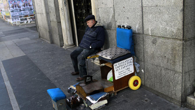 A shoeshiner sleeps as he waits for costumers in Madrid, Spain, Wednesday, Jan. 30, 2013. Spain's recession is worse than thought after official figures Wednesday showed the country's economy shrank 0.7 percent in the fourth quarter of 2012 from the previous three-month period. (AP Photo/Andres Kudacki)