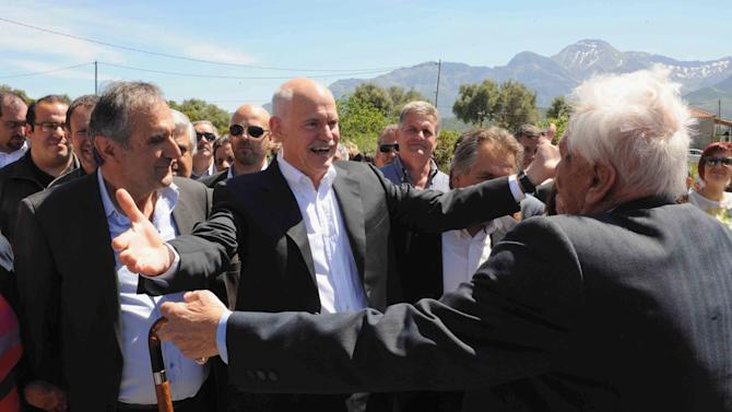 Former Socialist Prime Minister George Papandreou, 2nd left, is welcomed by supporters prior to casting his ballot in Kalentzi, western Greece Sunday May 6, 2012. Greeks head to the polls Sunday in their most critical and uncertain election in decades, with voters set to punish the two main parties that are being held responsible for the country's dire economic straits. (AP Photo/Yannis Androutsopoulos)