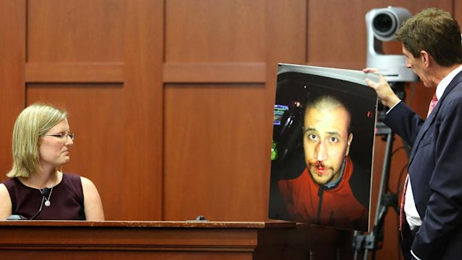Mark O'Mara, George Zimmerman's attorney, displays a photo of Zimmerman taken the night of the shooting of Trayvon Martin, to Zimmerman's physician, Lindzee Folgate, during her testimony on the 15th day of Zimmerman's trial in Seminole circuit court, in Sanford, Fla., Friday, June 28, 2013. Zimmerman has been charged with second-degree murder for the 2012 shooting death of Trayvon Martin.(AP Photo/Orlando Sentinel, Joe Burbank, Pool)