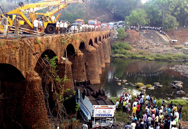 Rescuers and others gather at the site of a bus accident in Ratnagiri district, in the western Indian state of Maharashtra, Tuesday, March 19, 2013. The bus packed with passengers crashed through a gu