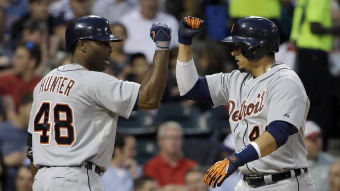 Detroit Tigers' Victor Martinez, right, celebrates with teammate Tori Hunter after hitting a solo home against the Chicago White Sox during the fifth inning of a baseball game in Chicago, Thursday, June 12, 2014. (AP Photo/Nam Y. Huh)