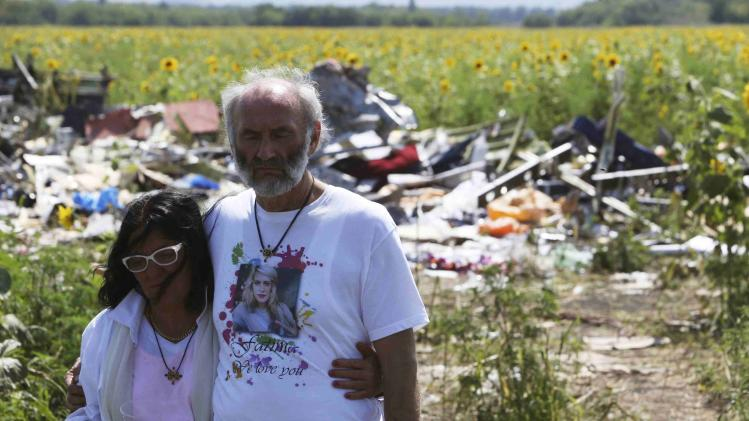 George and Angela Dyczynski walk near wreckage of the downed Malaysia Airlines Flight MH17, during their visit to the crash site near the village of Hrabove