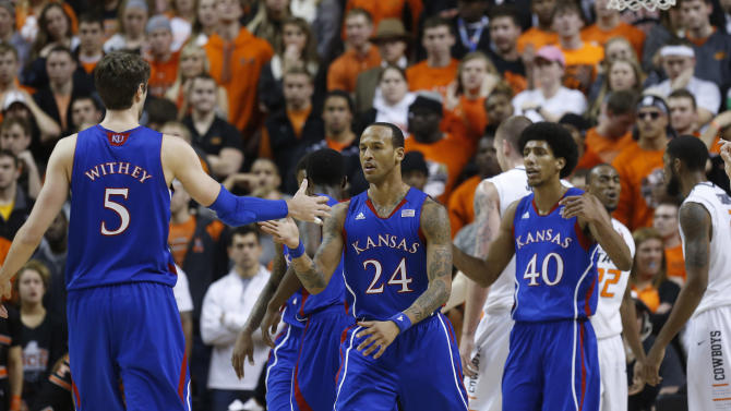 Kansas center Jeff Withey (5), guard Travis Releford (24) and forward Kevin Young (40) react after a foul call against Oklahoma State during the first half of an NCAA college basketball game in Stillwater, Okla., Wednesday, Feb. 20, 2013. (AP Photo/Sue Ogrocki)