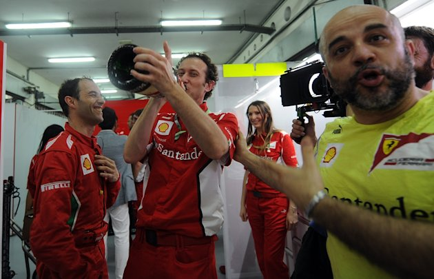 Crew members of winning Ferrari driver Fernando Alonso of Spain celebrate with champagne after Formula One's Malaysian Grand Prix at the Sepang International Circuit in Sepang on March 25, 2012. AFP P