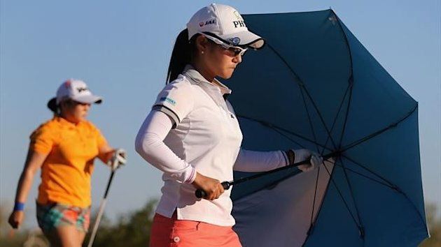Ai Miyazato of Japan holds an umbrella as she walks along the 18th hole during the first round of the RR Donnelley LPGA Founders Cup at Wildfire Golf Club (AFP)