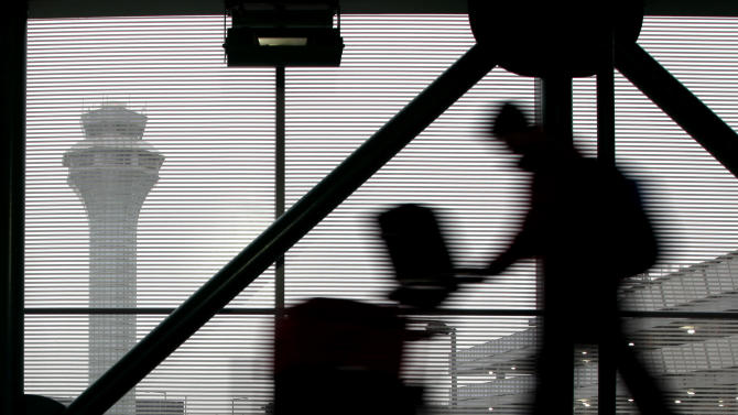 A traveler walks through Terminal 3 at O'Hare International Airport in Chicago on Saturday, Dec. 21, 2013. The National Weather Service issued a hazardous weather outlook for north central Illinois, northeast Illinois and northwest Indiana Saturday morning. (AP Photo/Nam Y. Huh)