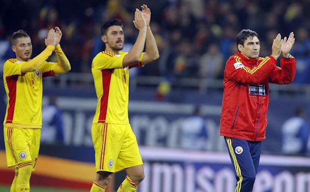 Romania's Ciprian Marica, center, applauds supporters with coach Victor Piturca, right, and teammate Gheorghe Grozav at the end of the World Cup Group D qualifying soccer match against Estonia at the