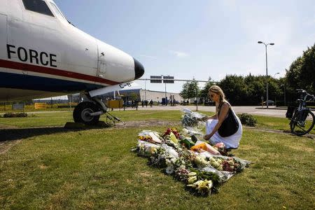 A local woman lays flowers in front of Dutch airplane during national day of mourning for Malaysia Airlines Flight MH17 victims in Eindhoven