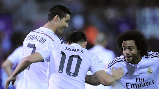 Real Madrid's James Rodriguez of Colombia, center, celebrates his goal with Cristiano Ronaldo of Portugal, left, and Marcelo of Brazil after scoring against SD Eibar, during their La Liga soccer match, at Ipurua stadium in Eibar, northern Spain, Saturday Nov. 22, 2014.  Real Madrid won 4-0