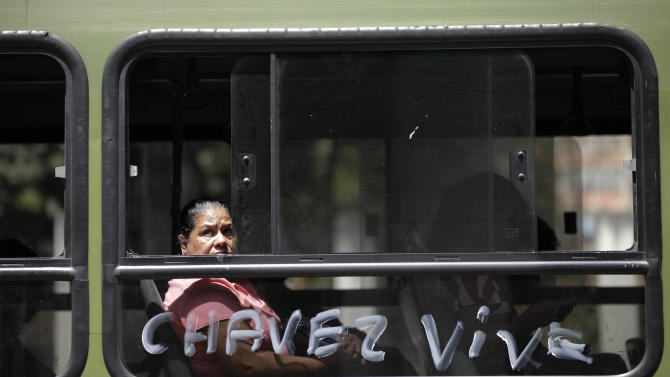 """A woman peers through a bus window that is covered in the Spanish words: """"Chavez is alive"""" near the military hospital where President Hugo Chavez is allegedly receiving treatment in Caracas, Venezuela, Wednesday, Feb. 20, 2013. Chavez's sudden return to Venezuela after more than two months of cancer treatments in Cuba has fanned speculation that the president could be preparing to relinquish power and make way for a successor and a new election. (AP Photo/Ariana Cubillos)"""