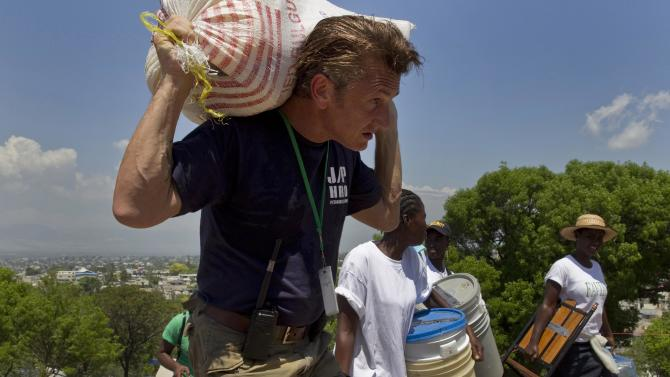 FILE - In this Saturday, April 10, 2010 file photo, U.S. actor Sean Penn carries the belongings of a person displaced by the earthquake as people are relocated from the Petionville Golf Club to a new camp, Corail-Cesselesse, in Port-au-Prince, Haiti. The actor who stormed onto the scene of one of the worst natural disasters in history two years ago has certainly not lost interest. Defying skeptics, he has put down roots in Haiti, a country he hadn't even visited before the January 2010 earthquake, and has become a major figure in the effort to rebuild. (AP Photo/Ramon Espinosa)