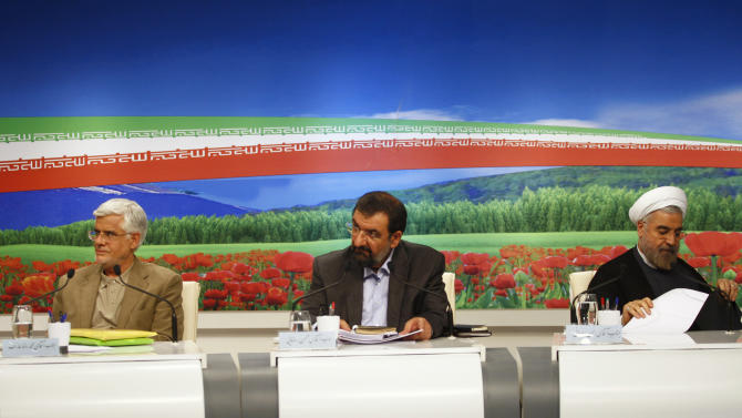 "In this photo released by the Islamic Republic of Iran Broadcasting on Friday, May 31, 2013, presidential candidates from left, Mohammad Reza Aref, Mohsen Rezaei, and Hasan Rowhani, attend a TV debate, in a state-run TV studio, in Tehran, Iran. A hard-liner calls for ""reconciliation with the world"" as Iran's ailing economy takes center stage at the first presidential debate by eight candidates to replace Mahmoud Ahmadinejad. The hopefuls, vetted by the country's ruling clerics, argue about how to deal with high inflation and unemployment, stemming in part from international sanctions over the Islamic Republic's disputed nuclear program. (AP Photo/Islamic Republic of Iran Broadcasting, Mehdi Dehghan)"
