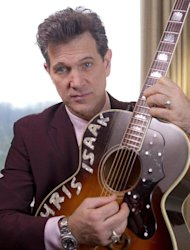 "U.S musician Chris Isaak plays on his guitar during an interview with Associated Press Television in a west London hotel, to promote the launch of his new album ""Beyond The Sun"", Tuesday, Jan. 24, 2012. (AP Photo/Joel Ryan)"