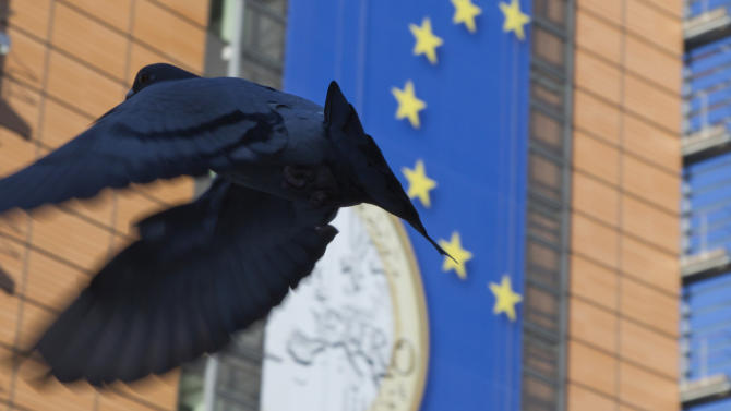A pigeon flies in front of a giant banner for the euro currency in front of EU headquarters in Brussels on Tuesday, Nov. 20, 2012. European Union officials will make a fresh try Tuesday to reaching a political accord on desperately needed bailout loans to Greece, an agreement that eluded them last week. (AP Photo/Virginia Mayo)