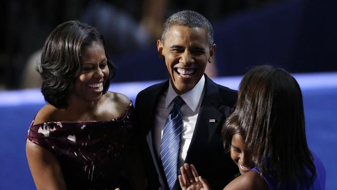 "FILE - In this Sept. 6, 2012 file photo, President Barack Obama laughs with his wife Michelle and his daughters Malia and Sasha after his speech to the Democratic National Convention in Charlotte, N.C.  Call it the campaign trail schtick. Have you heard the one about the kid who thinks President Barack Obama's job is to ""approve this message?"" Or the time Mitt Romney compared another presidential run to giving birth? The jokes at presidential fundraisers and rallies are easy applause lines for Obama and Romney, a way to keep supporters entertained before more weighty subjects like Medicare, taxes and foreign policy. A good sense of humor has served presidential candidates well in the past. So it's little wonder why both Obama and Romney are using the same technique.  (AP Photo/Lynne Sladky, File )"