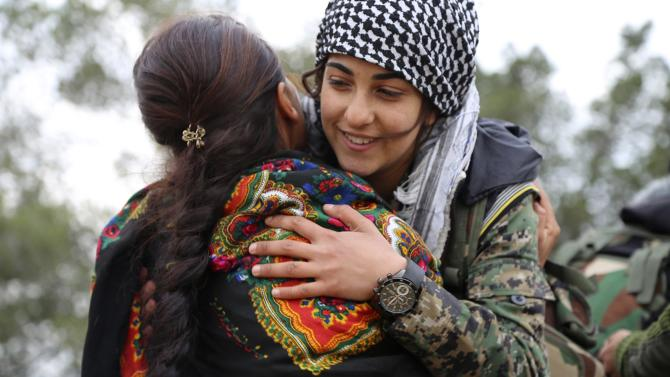A Kurdish People's Protection Units (YPG) fighter hugs a fellow fighter in a YPG military base east of Qamishli, before heading to Jazaa and Tal Kojar frontlines