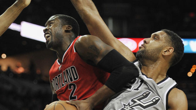 Portland Trail Blazers guard Wesley Matthews, left, is defended by San Antonio Spurs forward Tim Duncan during the first half of an NBA basketball game, Friday, Dec. 19, 2014, in San Antonio. (AP Photo/Darren Abate)