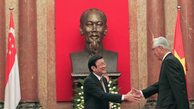 Singapore's ESM Goh is greeted by Vietnam's President Sang front of a statue of late Vietnamese revolutionary leader Ho Chi Minh at the Presidential Palace in Hanoi