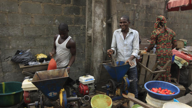 Men grind pepper at a market in Obalende  Lagos, Nigeria, Saturday, Jan. 14, 2012.  Nigeria's government will meet with labor unions in a last bid to halt a paralyzing national strike that now threatens oil production in Africa's most populous nation.  (AP Photo/Sunday Alamba)