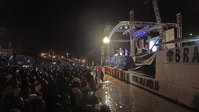 In this photo taken early Sunday, Feb. 9, 2014, Malian singer Salif Keita, rear center, performs on stage at a music festival at Segou, Mali. Long before Mali captured the global spotlight as an al-Qaida training ground where French soldiers had to intervene, the West African nation was celebrated for producing some of the biggest stars in world music. (AP Photo/Baba Ahmed)