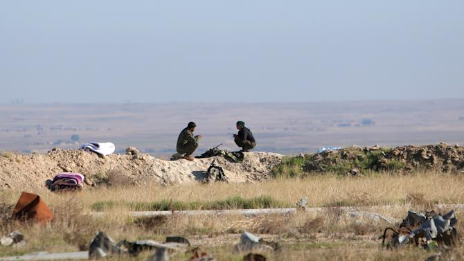 Fighters from the Democratic Forces of Syria sit at one of their guard posts in the 121 Regiment base, after they took control of it from Islamic State militants, in the town of al-Melabiyyah, south of Hasaka city, Syria