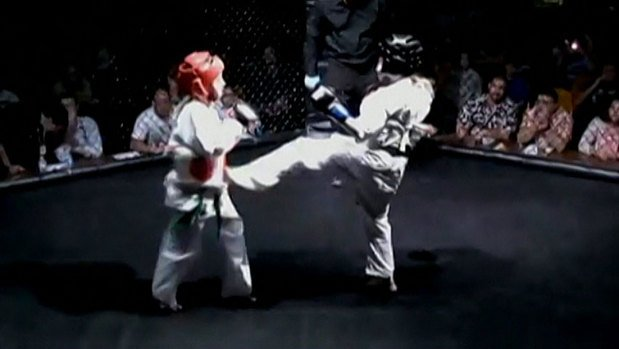 Children take part in a mixed martial arts cage fight.