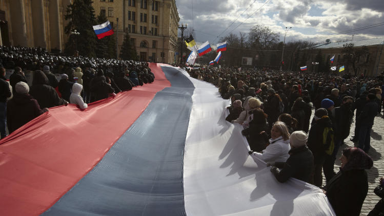 In this photo taken on Sunday, March 16, 2014, Pro-Russia demonstrators chant slogans as they carry a giant flag during a rally at a central square in Kharkiv, Ukraine. Thousands of pro-Russia demonstrators gathered in the Ukraine's northeastern town to show their support for the Crimean referendum. (AP Photo/Sergey Kozlov)